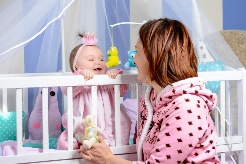 Young mother hugs her little daughter in the room stock photography