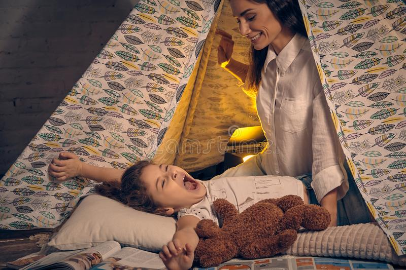 Mother and her daughter are in a teepee tent with some pillows. Happy family. Young mother and her pretty daughter are in a teepee tent with some pillows. Girl stock photo