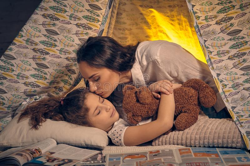 Mother and her daughter are in a teepee tent with some pillows. Happy family. Young mother and her pretty daughter are in a teepee tent with some pillows. Girl stock images