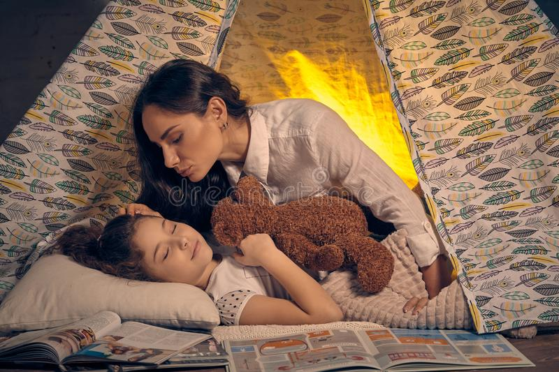 Mother and her daughter are in a teepee tent with some pillows. Happy family. Young mother and her pretty daughter are in a teepee tent with some pillows. Girl royalty free stock photos