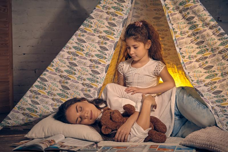 Mother and her daughter are in a teepee tent with some pillows. Happy family. Young mother and her pretty daughter are in a teepee tent with some pillows. Mom stock image