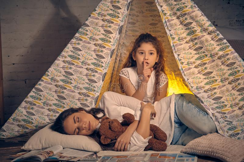 Mother and her daughter are in a teepee tent with some pillows. Happy family. Young mother and her pretty daughter are in a teepee tent with some pillows. Mom royalty free stock photography