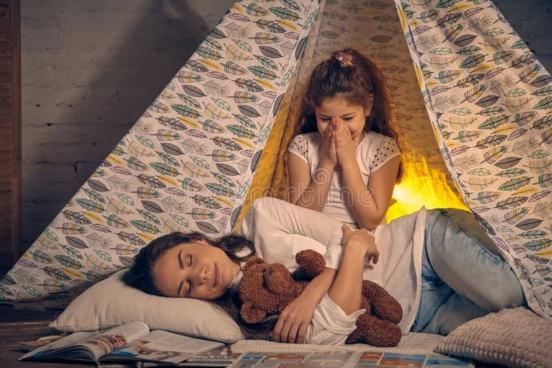 Mother and her daughter are in a teepee tent with some pillows. Happy family. Young mother and her pretty daughter are in a teepee tent with some pillows. Mom stock images