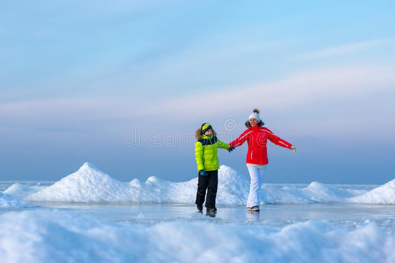 Young mother and her son on icy beach stock photos