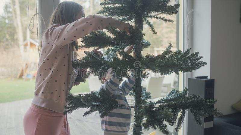Young mother and her son making an artificial  christmas tree royalty free stock images