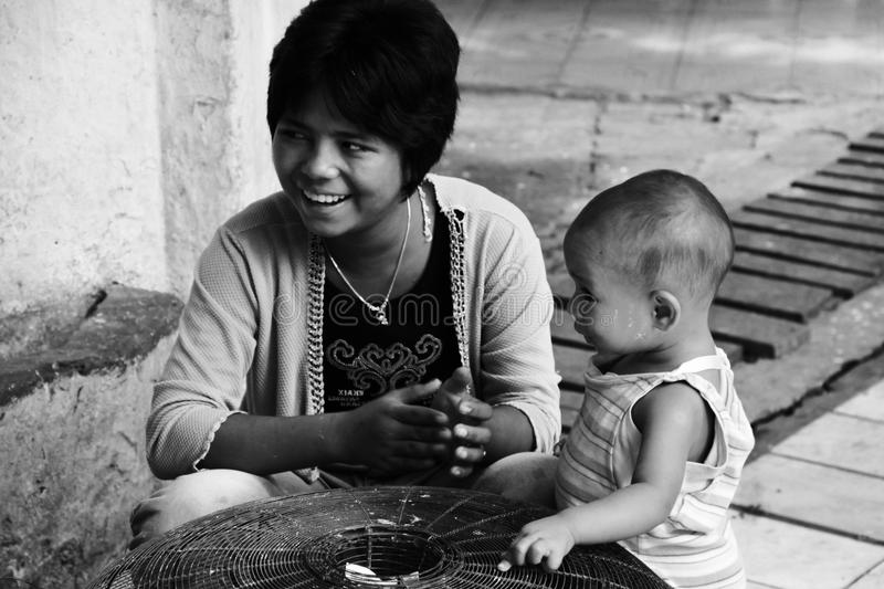 Young mother and her son, Myanmar. Young mother and her son, selling birds to free in a buddhist temple in Mandalay, Myanmar stock images