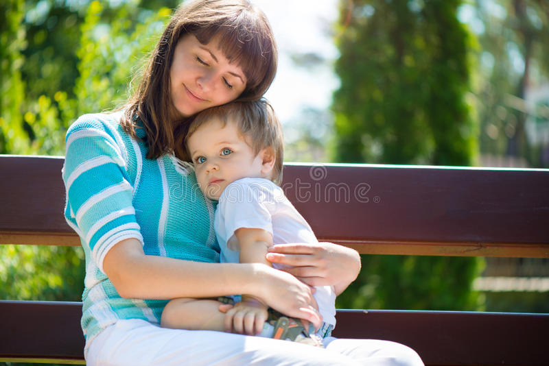 Young mother with her son in park royalty free stock image