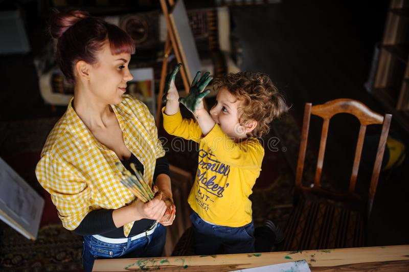 Young mother and her son playing with color paints stock image