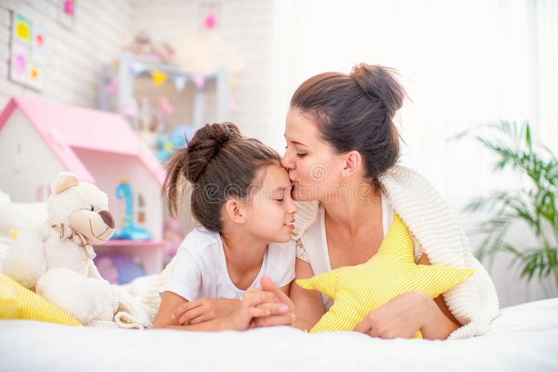 A young mother and her teenage daughter are lying on the bed royalty free stock photos