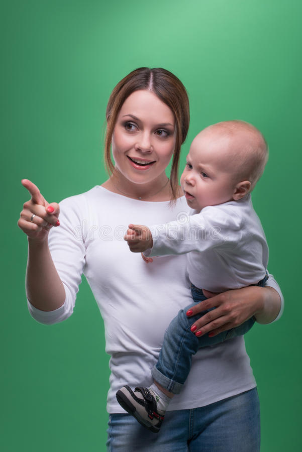 Young mother and her toddler son pointing at stock images