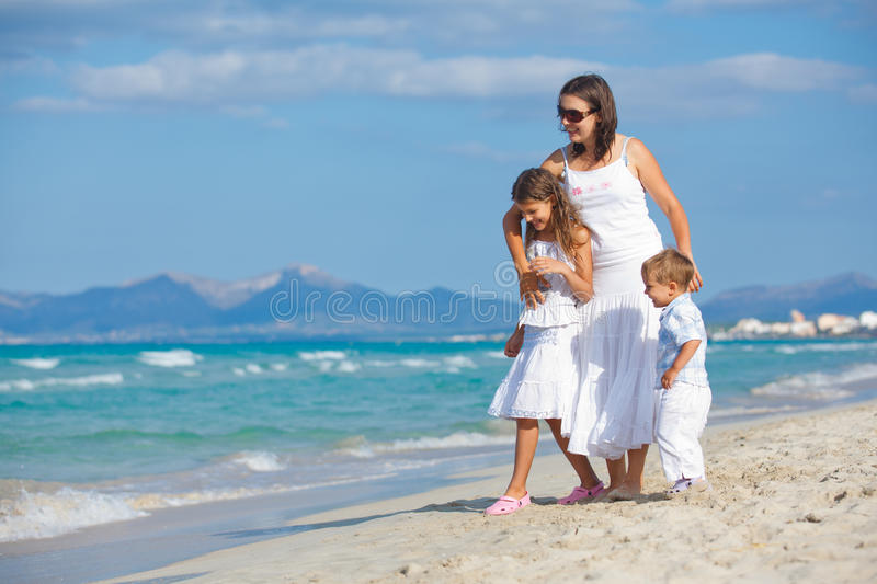 Young mother with her two kids on beach vacation stock image