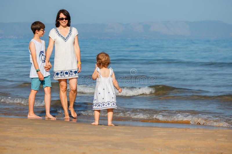 Young mother with her two kids on tropical beach vacation stock photo