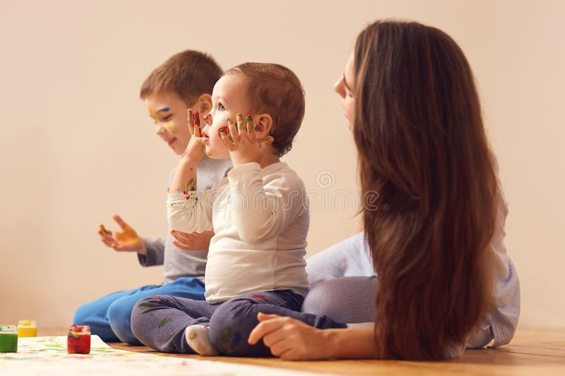 Young mother and her two little sons dressed in home clothes are sitting on the wooden floor in the room and painting. With fingers on the white paper royalty free stock photo