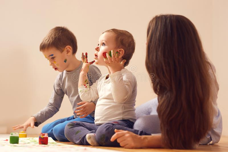 Young mother and her two little sons dressed in home clothes are sitting on the wooden floor in the room and painting. With fingers on the white paper stock photography