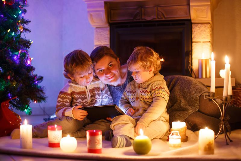 Young mother and his little children sitting by a fireplace on C royalty free stock image