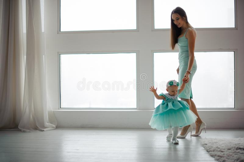 Young mother hold her daughter hand and walking in the room stock image
