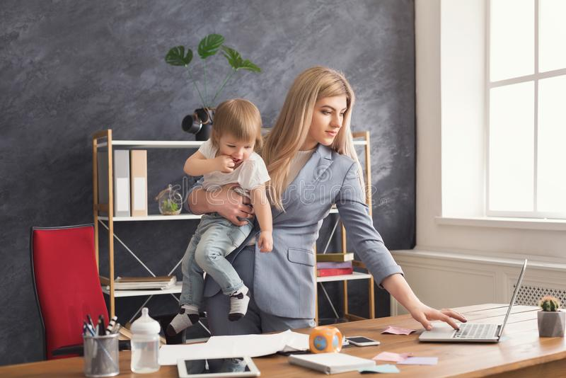 Young mother holding baby while using laptop royalty free stock images