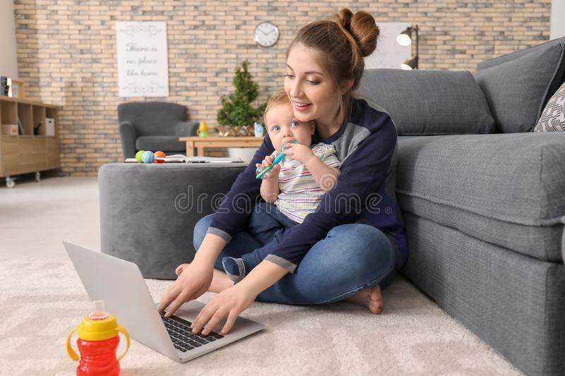 Young mother holding baby while working at home royalty free stock photos
