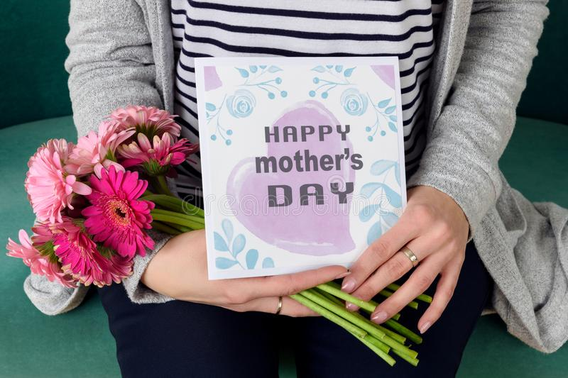 Young mother holding bouquet of gerbera daisies and mother`s day greeting card sitting on a couch. royalty free stock photography