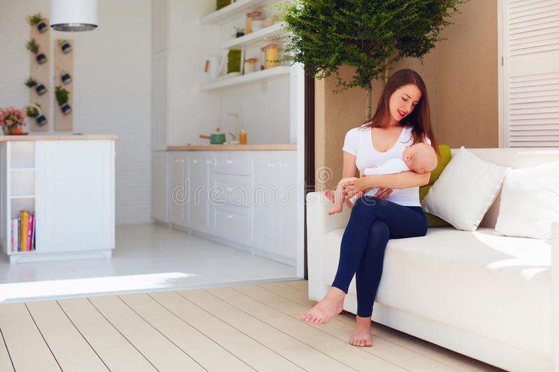 Young mother holding on hands infant baby, while sitting on open space kitchen stock photography