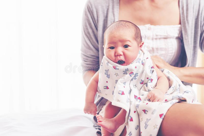 Young mother holding her newborn baby girl, one week daughter royalty free stock photo