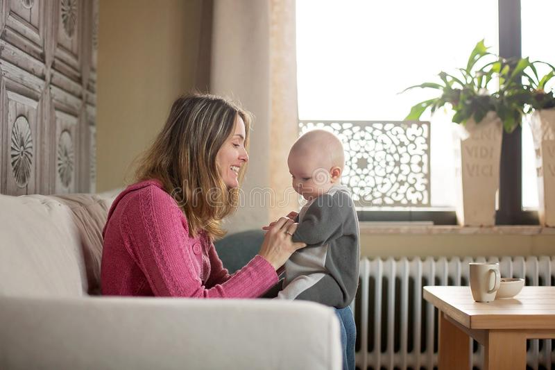 Young mother, holding her toddler boy, breastfeeding him at home. Sunny living room royalty free stock image