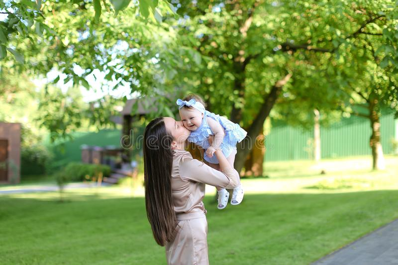 Young mother holding little female baby in garden. royalty free stock photography