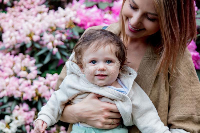 Mother holding a male baby near a blossom flowers. Young mother holding a male baby near a blossom flowers in park. Spring time season stock image