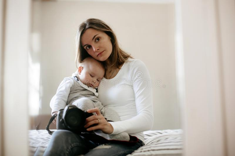 Young mother, holding tenderly her sleeping toddler boy. Taking picture through a mirror, sunny living room stock photos