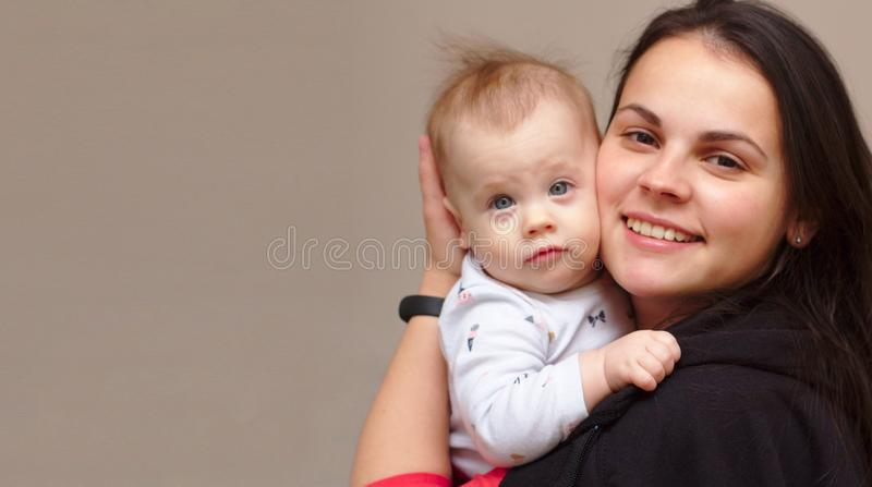 young mother holds her funny, sweet baby in her arms stock image