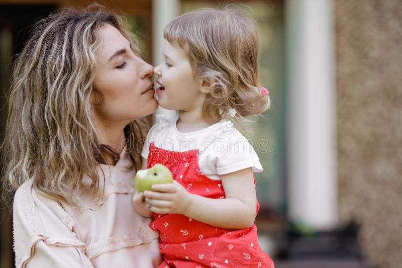Young mother holds her little daughter on her hands and kisses her in the garden on a warm summer day royalty free stock image
