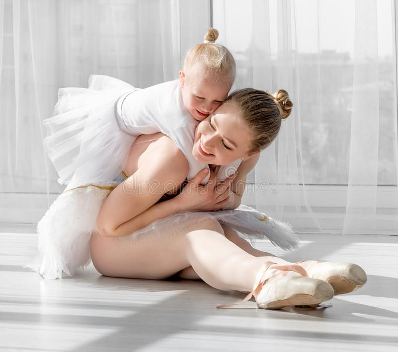 Young mother hugging little smiling daughter in ballet studio stock image