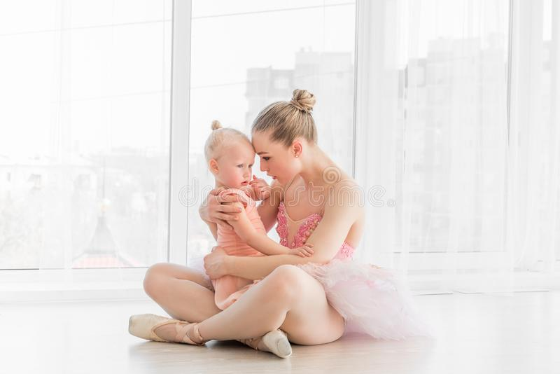 Young mother hugging little smiling daughter in ballet studio stock photography