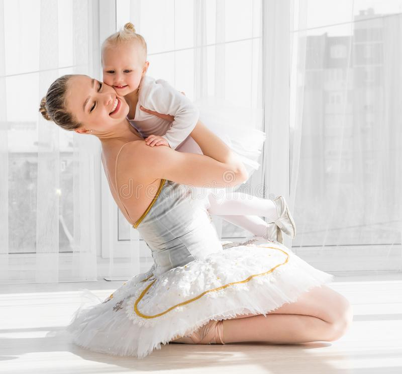 Young mother hugging little smiling daughter in ballet studio stock images