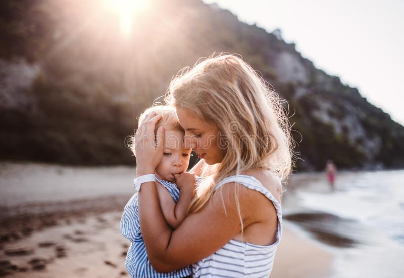 Young mother with a toddler girl on beach on summer holiday at sunset. royalty free stock images
