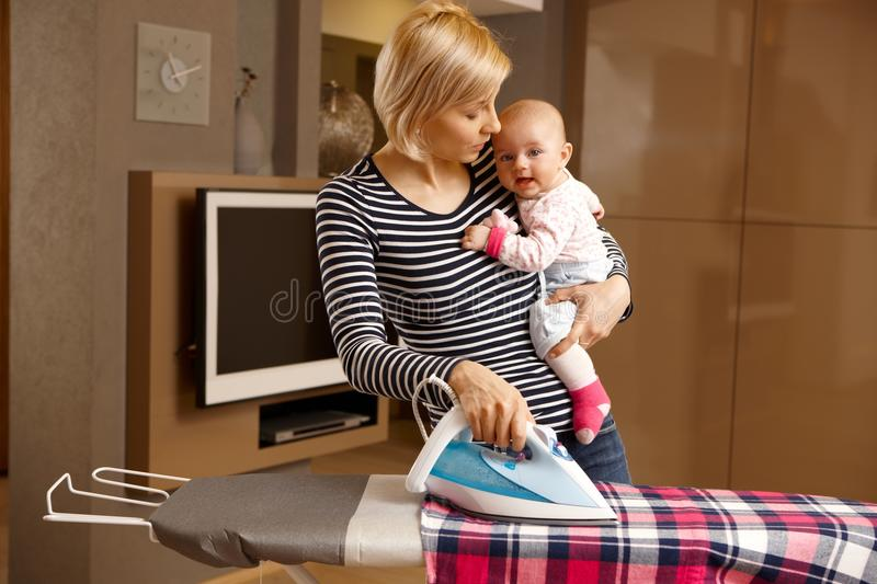 Young mother ironing with baby in arm. Young mother ironing while holding baby in arm royalty free stock images