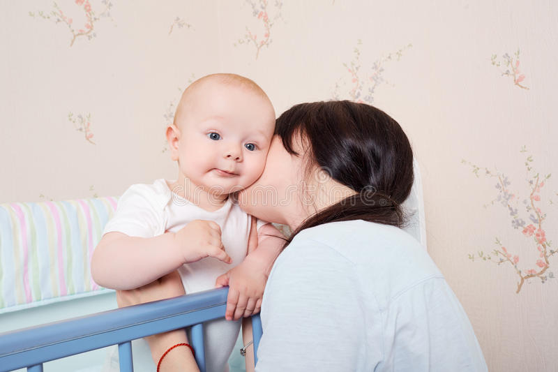 Young mother kissing baby boy, hugging in a cot. stock image