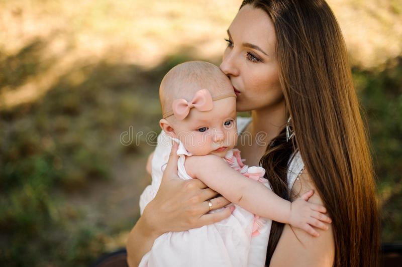 Young mother kissing cute baby girl walking in park. Young mother kissing cute blue-eyed baby girl walking in the park on sunny summer day royalty free stock photo