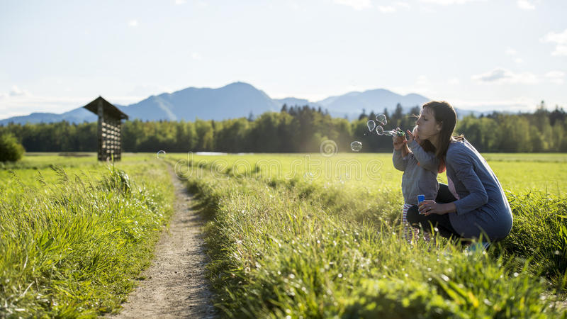 Young mother kneeling down to her child blowing soap bubbles tog royalty free stock photography