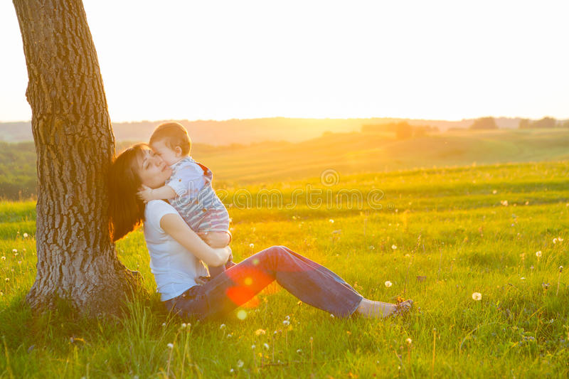 Young mother with little baby boy sitting at sunset stock images