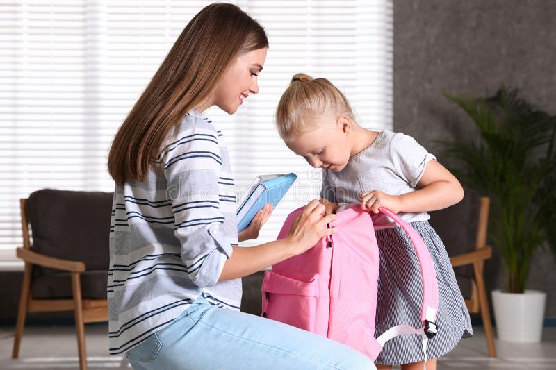Young mother and little child putting textbooks into school bag stock images