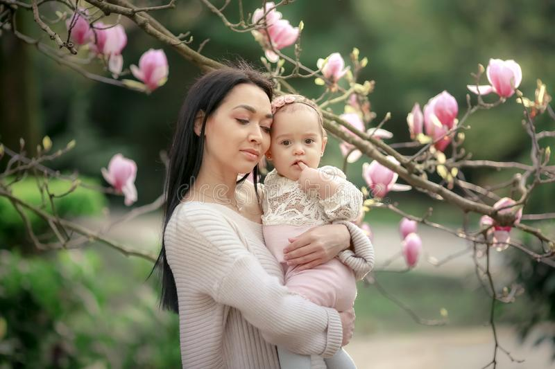 Young mother and little daughter in autumn park play with magnolia leaves. Happy weekend with family in autumnal forest royalty free stock image