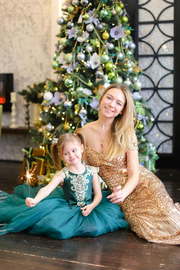 Young mother and little daughter with bengal light sitting on floor near Christmas tree. stock image
