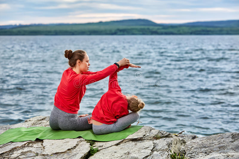 Young mother and little daughter doing yoga exercises on the stone near river. royalty free stock photography