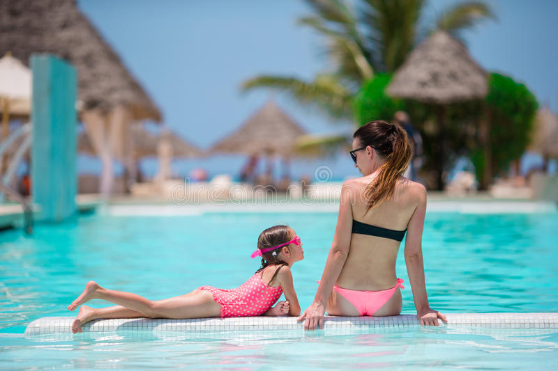 Young mother and little daughter have fun on the edge of swimming pool royalty free stock photography