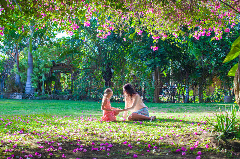 Young mother with little daughter in the lush. Young mother and her little daughter sitting in the lush garden and enjoy the rest stock image