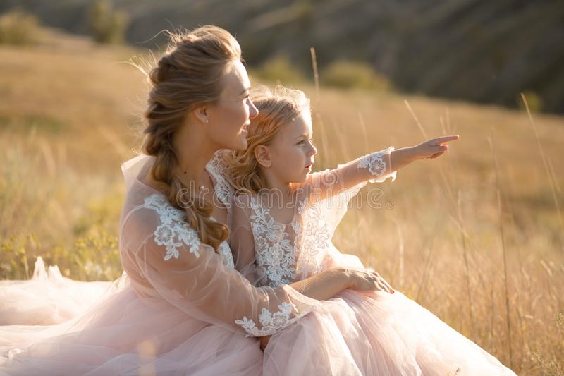 Young mother with a little daughter in pink dresses are sitting in the field. Mom hugs daughter, hugging her. point finger into stock image