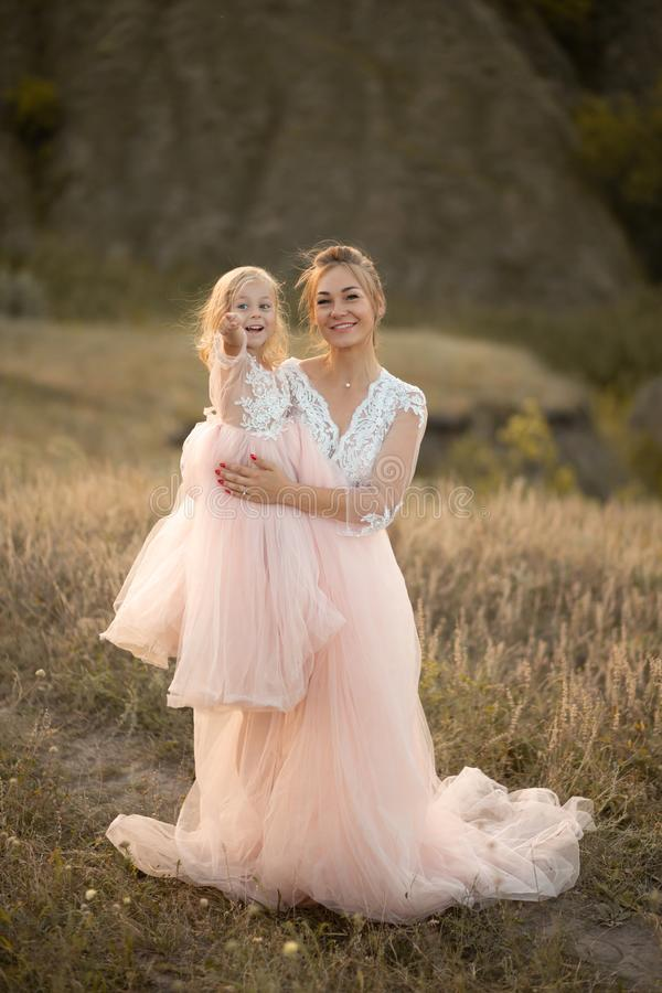 Young mother with a little daughter in pink dresses are sitting in the field. Mom hugs daughter, hugging her. point finger into royalty free stock photo