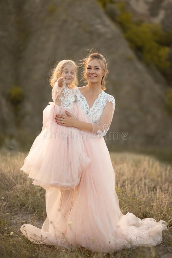 Young mother with a little daughter in pink dresses are sitting in the field. Mom hugs daughter, hugging her. point finger into royalty free stock photography