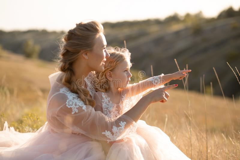 Young mother with a little daughter in pink dresses are sitting in the field. Mom hugs daughter, hugging her. point finger into stock images